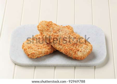 Breaded fish fillets on a cutting board - stock photo