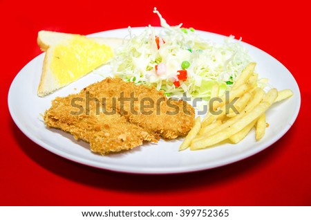 Breaded fish steak with salad, french fries and toast. (Selective focus) - stock photo