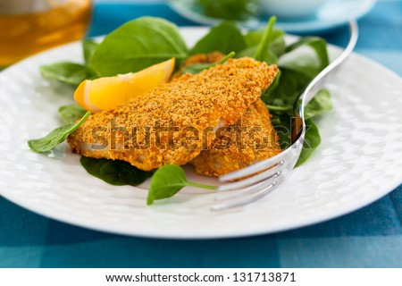breaded fish with spinach - stock photo