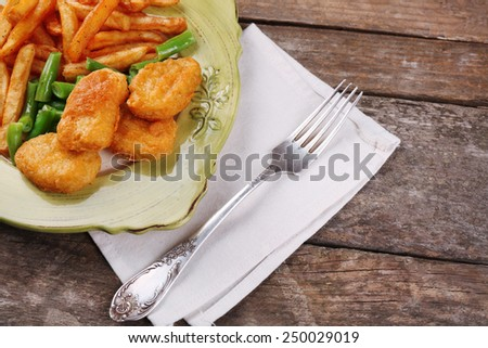 Breaded fried chicken nuggets and potatoes with asparagus on plate with napkin on wooden planks background - stock photo