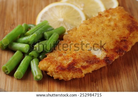 Breaded fried fillet and potatoes with asparagus and sliced lemon - stock photo