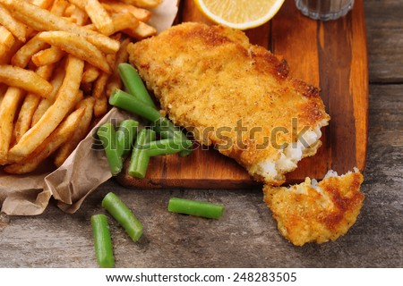Breaded fried fish fillet and potatoes with asparagus and lemon on cutting board and rustic wooden background - stock photo