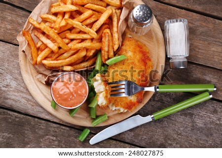 Breaded fried fish fillet and potatoes with asparagus and sauce on cutting board and rustic wooden background - stock photo