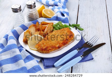 Breaded fried fish fillet and potatoes with asparagus and sliced lemon on plate with napkin on color wooden planks background - stock photo