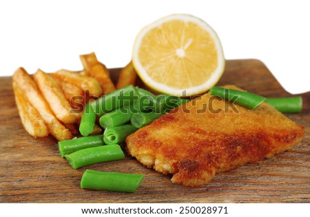 Breaded fried fish fillet and potatoes with asparagus and sliced lemon on wooden cutting board isolated on white - stock photo