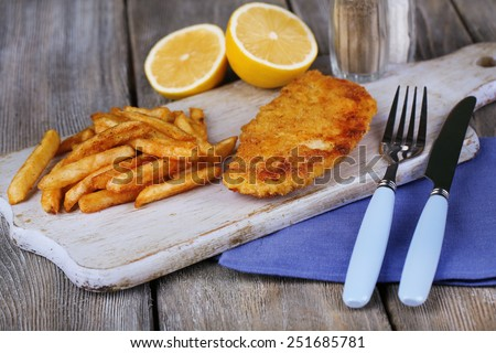Breaded fried fish fillet and potatoes with sliced lemon and cutlery on cutting board and wooden planks background - stock photo