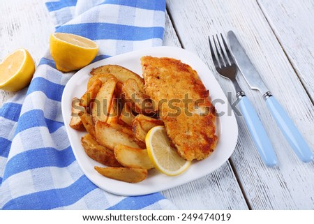 Breaded fried fish fillet and potatoes with sliced lemon on plate with napkin on color wooden planks background - stock photo
