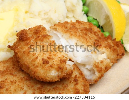 Breaded haddock fish fillets served with mash and peas. - stock photo