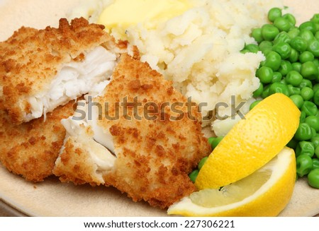 Breaded haddock fish fillets served with peas and mash - stock photo