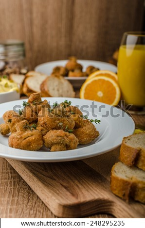 Breaded mushrooms fried with fresh orange juice and homemade tartar sauce - stock photo