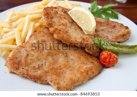 Breaded pork chop with frites and vegetables