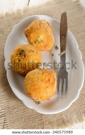 breaded potato balls with thyme and fork in a bowl - stock photo