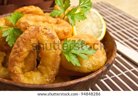 Breaded squids slices baked on deep oil - stock photo