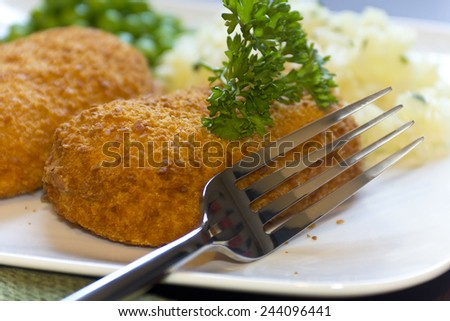 Breaded stuffed chicken cordon bleu with green peas white rice and parsley for garnish - stock photo