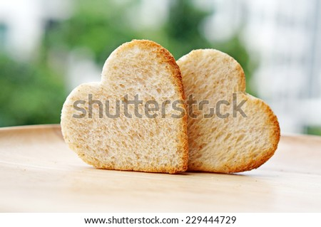 Breads cutting in shape of heart with nature background. Concept about love and relationship.                      - stock photo