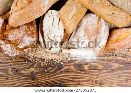 Breads with wheat seeds and flour on burlap and wooden background - stock photo