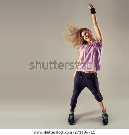 Break dance party. Stylish smiling fit woman dancing on studio background. Sport and recreation concept.  - stock photo