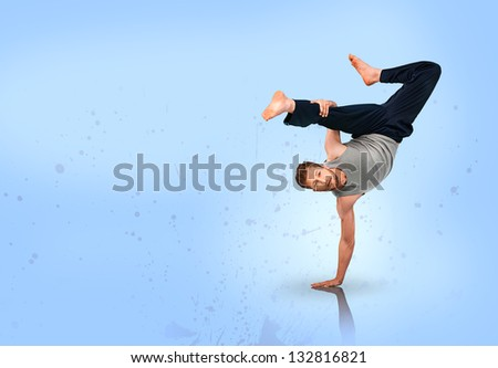 Break dancer doing handstand on blue background - stock photo