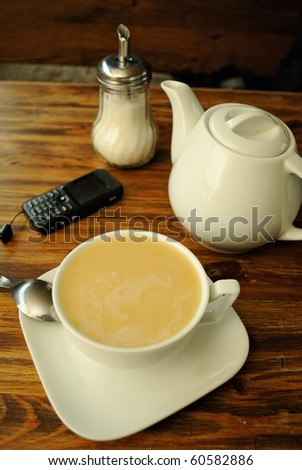 Break for tea in cafe. A cup of tea, sugar bowl, spoon, teapot and cellphone on the table. - stock photo