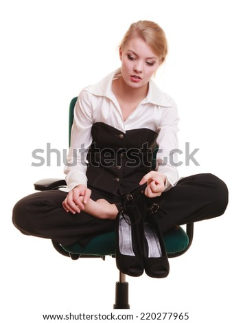 Break from work. Tired businesswoman with leg pain. Young woman massaging her feet on chair isolated on white.