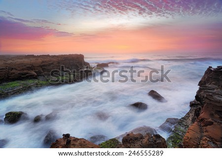 Break of dawn the rosy flamingo feathered sunrise skies compete for attention with turbulent rushing ocean flows over tidal rocks - stock photo