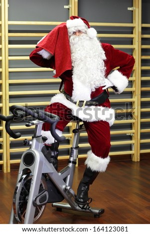 break - Santa Claus training on exercise bike at the gym - stock photo