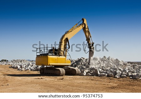 Breaker used to break up boulders in an open cast mine - stock photo
