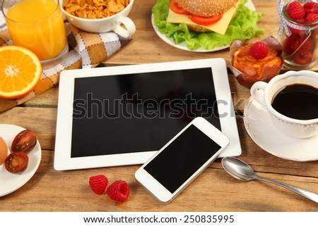 breakfast and mobile phone on wooden table - stock photo