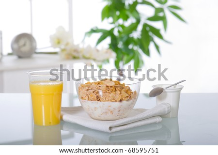 breakfast at home  with cereal orange juice and yogurt over glass table - stock photo