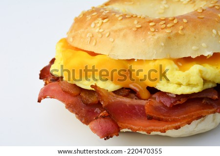 Breakfast bagel with scrambled eggs, cheese and bacon. Breakfast sandwich. Isolated. Close up.  - stock photo