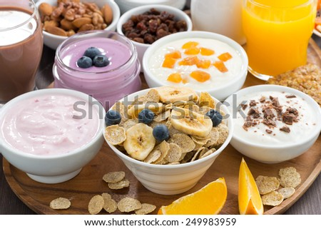 breakfast buffet with cereals, yoghurt and fruit on wooden tray, close-up, horizontal - stock photo