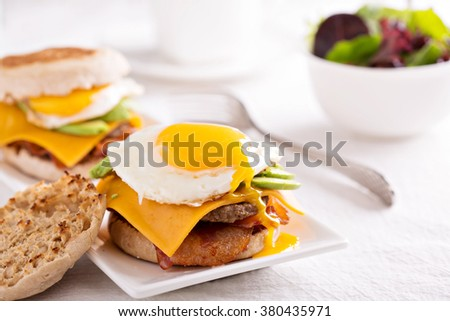 Breakfast burger with fried egg and avocado, cheese and bacon - stock photo