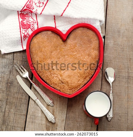 breakfast cake inside heart baking tin over wood with vintage silverware and milk mug - stock photo