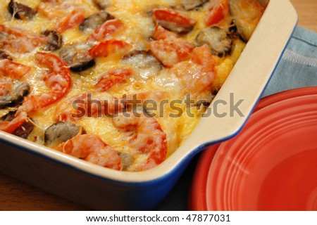 Breakfast casserole with eggs, sausage, tomatoes, potatoes, onion and cheese