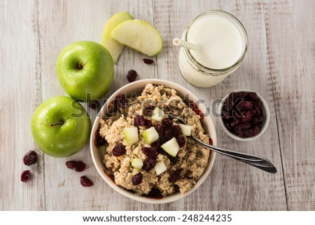 Breakfast cereal healthy oatmeal with cranberries and apples and glass of milk - stock photo