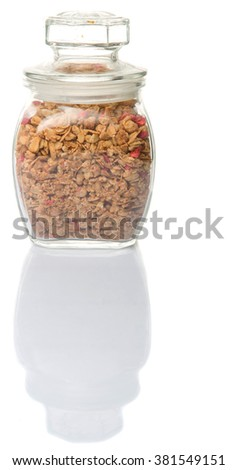 Breakfast cereal with dried raspberry fruit pieces in glass jar over white background