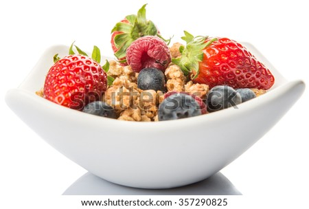 Breakfast cereal with strawberry, raspberry and blueberry in white bowl over white background - stock photo