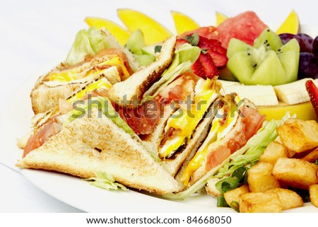 Breakfast club sandwich and assorted fruits on white plate