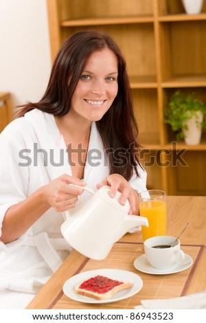 Breakfast coffee and toast happy woman in home bathrobe - stock photo