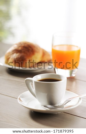 Breakfast, coffee, Croissant and Orange juice  on wooden table