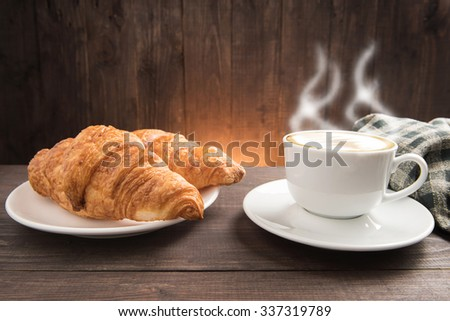 Breakfast coffee cup and croissant on wooden background.