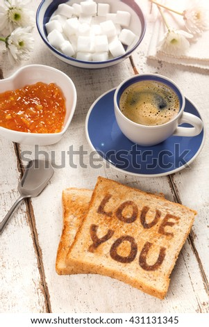 Breakfast, coffee, jam and toast with the text love you - stock photo