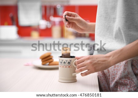 Breakfast concept. Woman holding cup of tea in kitchen