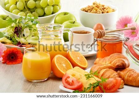 Breakfast consisting of fruits, orange juice, coffee, honey, bread and egg. Balanced diet - stock photo