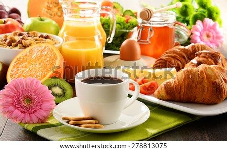 Breakfast consisting of fruits, orange juice, coffee, honey, bread and egg. Balanced diet. - stock photo