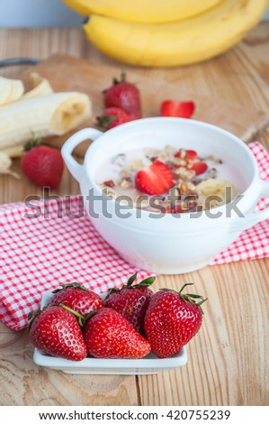 breakfast consisting of vanilla greek yogurt topped with granola, sliced bananas and strawberries, on an old wooden textured table with red fabric