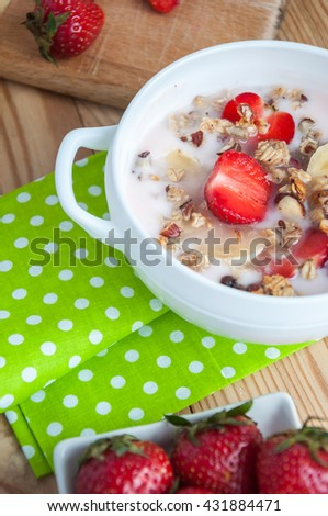 breakfast consisting of vanilla greek yogurt topped with granola, sliced bananas and strawberries, on an old wooden textured table with green fabric - stock photo