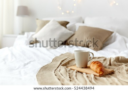 breakfast, coziness, morning, holidays and winter concept - cozy bedroom with coffee cup and croissant on wooden board in bed at home