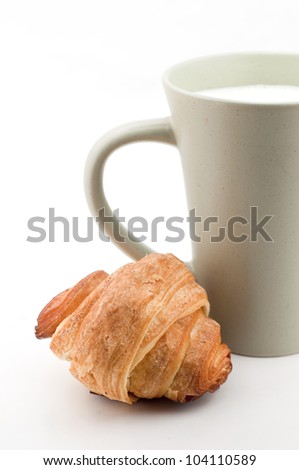 Breakfast - cup of milk and croissant - stock photo