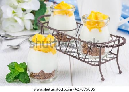 Breakfast dessert with bran flakes, plain yogurt and mango, in iron tray - stock photo